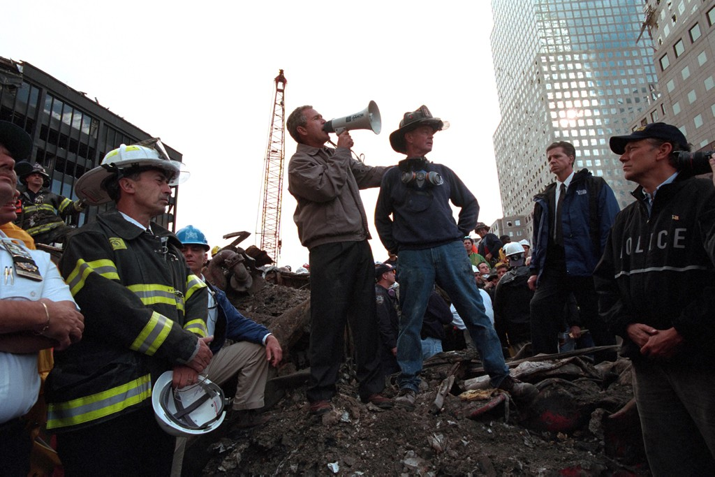 """Standing on top of a crumpled fire truck with retired New York City firefighter Bob Beckwith, President George W. Bush rallies firefighters and rescue workers Friday, Sept. 14, 2001, during an impromptu speech at the site of the collapsed World Trade Center towers in New York City. """"I can hear you,"""" President Bush said. """"The rest of the world hears you. And the people who knocked these buildings down will hear all of us soon."""" Photo by Eric Draper, Courtesy of the George W. Bush Presidential Library"""