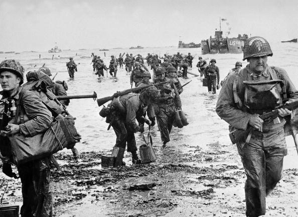 FRANCE - JUNE 06:  American soldiers, their feet in water, are landing on a Normandy beach. In the background are the American military ships which transported them.  (Photo by Keystone-France/Gamma-Keystone via Getty Images) spectator.org